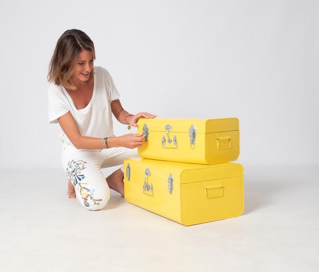 Ragazza bionda vestita di bianco pone accanto a due valigie metalliche gialle.