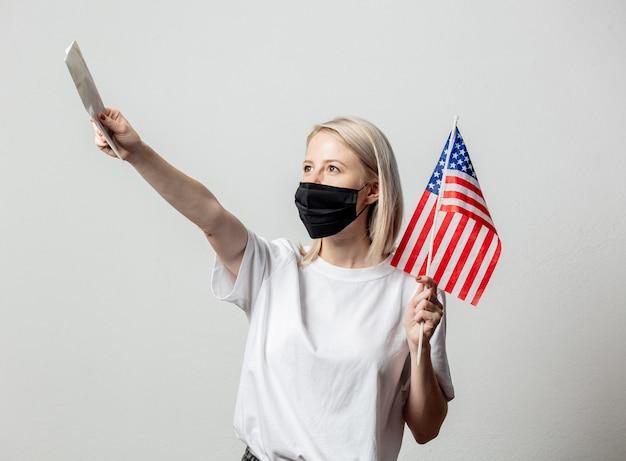 Ragazza bionda in maschera facciale con bandiera usa e denaro