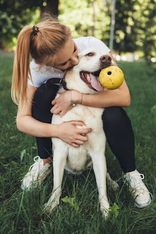 Ragazza bionda e il suo golden retriever che giocano con una palla sull'erba