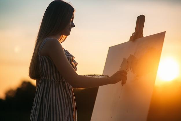 Ragazza bionda dipinge un dipinto sulla tela all'aperto al tramonto