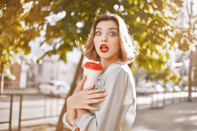 Ragazza bionda nel parco all'aperto in estate con una tazza di caffè
