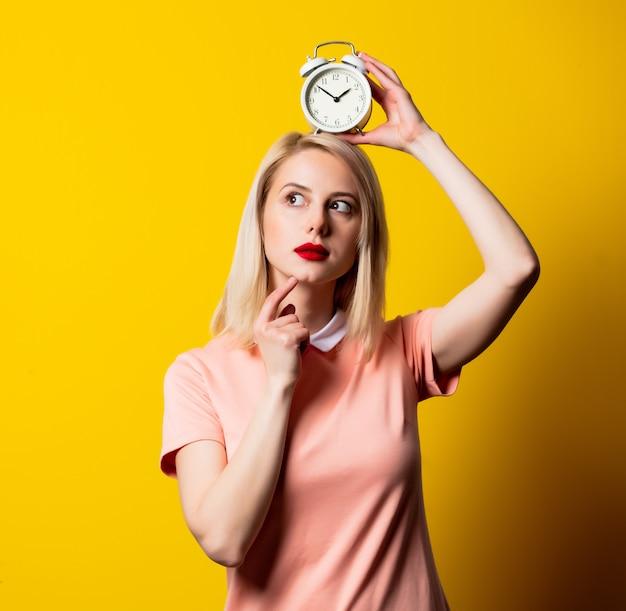 Ragazza bionda in vestito rosa con la sveglia su spazio giallo