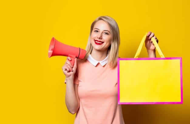 Ragazza bionda in abito rosa con la borsa della spesa e il megafono