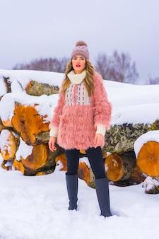 Ragazza bionda in una giacca di pelliccia rosa e un cappello viola nella neve. accanto ad alcuni alberi tagliati con ghiaccio, stile di vita invernale