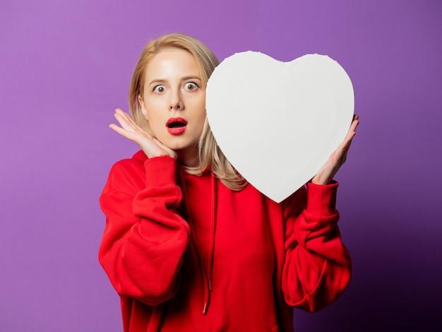 Ragazza bionda in felpa rossa tenere il cuore