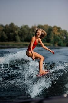 Ragazza bionda che guida sul wakeboard rosso sul lago