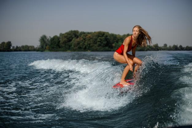Ragazza bionda che guida sul wakeboard rosso