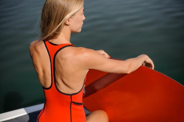 Ragazza bionda che si siede vicino al lago con un wakeboard rosso
