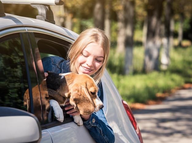 Ragazza bionda che si siede con il cucciolo in macchina