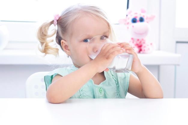 La ragazza bionda sorride e beve il latte. sfondo chiaro.