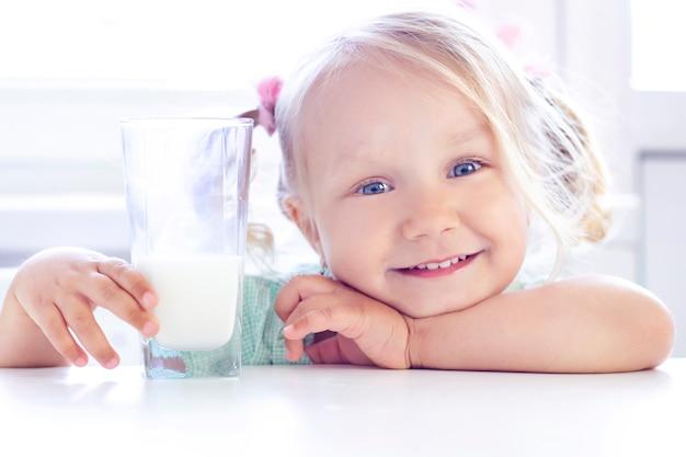 La ragazza bionda sorride e beve il latte.