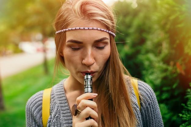 Ragazza bionda che fuma sigaretta elettronica.