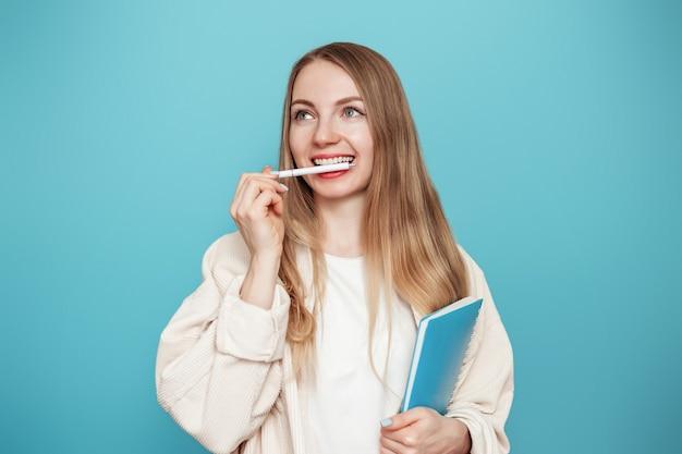 Studentessa bionda premurosa, sognando ad occhi aperti e ha morso la sua maniglia con i suoi denti isolati su una parete blu dello studio. concetto di educazione