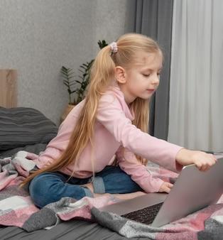 Ragazza bionda studia a casa online con un laptop a letto