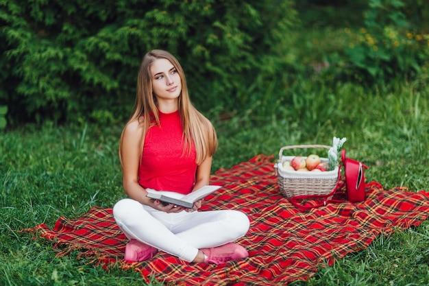 Ragazza bionda che pensa alla vita nel parco con il suo libro preferito.