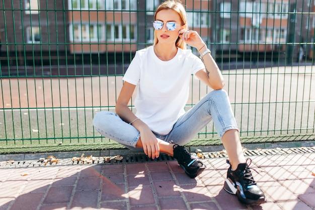 Ragazza bionda che indossa t-shirt e occhiali in posa contro la strada