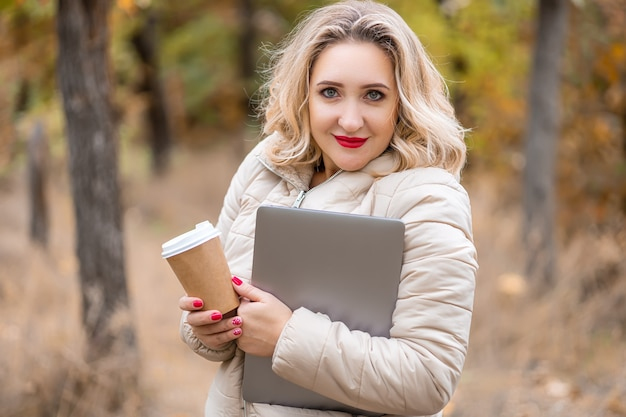 Una ragazza bionda che si trova in un parco autunnale stringeva un laptop e una tazza di caffè