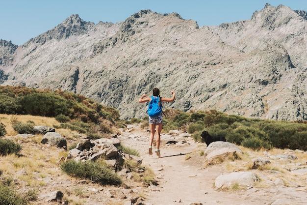 Ragazza bionda con trecce e zaino blu che salta con il suo cane attraverso la montagna.