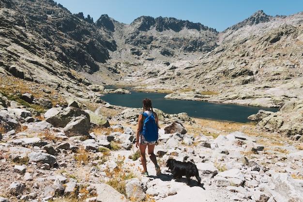 Ragazza bionda con trecce e zaino blu che cammina con il suo cane attraverso la montagna.