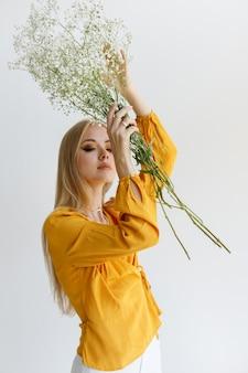 Ragazza bionda con fiori secchi su sfondo chiaro. atmosfera romantica