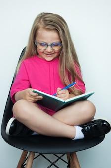 Ragazza bionda con gli occhiali sta scrivendo qualcosa in un libro mentre posa in una poltrona su un muro bianco