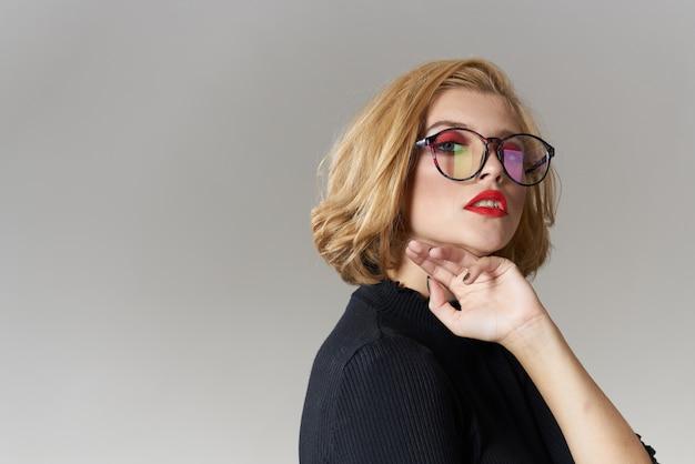 Ragazza bionda con gli occhiali labbra rosse camicetta nera vista ritagliata studio sfondo chiaro glamour.