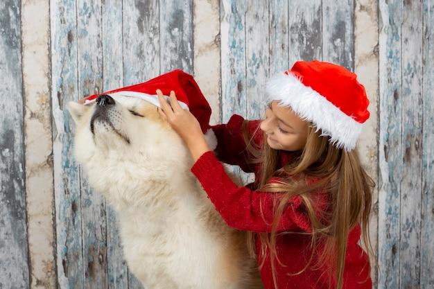 Ragazza bionda con il suo cane con il cappello della santa, mettendo il cappello sul suo cane, celebrando la parete di legno di natale