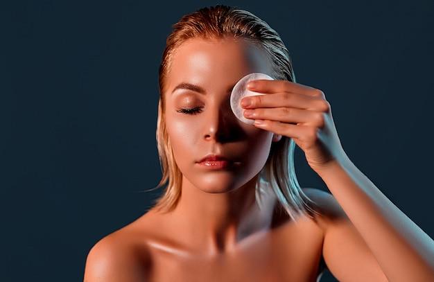 Ragazza bionda con pelle perfetta che applica balsamo sugli occhi con il cuscinetto rotondo bianco sulla parete nera.