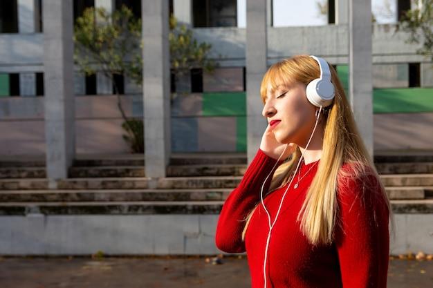 Ragazza bionda con rossetto rosso e maglione rosso che ascolta la musica con il telefono e le cuffie nel parco.