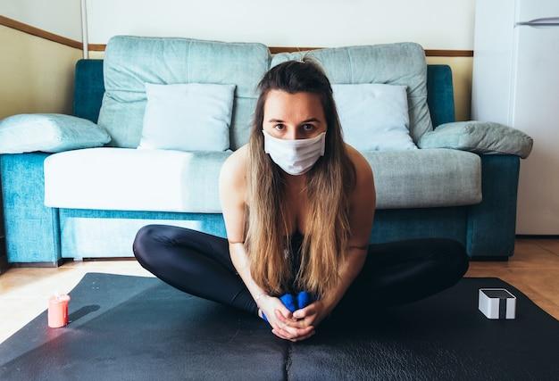 Ragazza bionda con mascherina chirurgica facendo yoga e meditazione a casa.