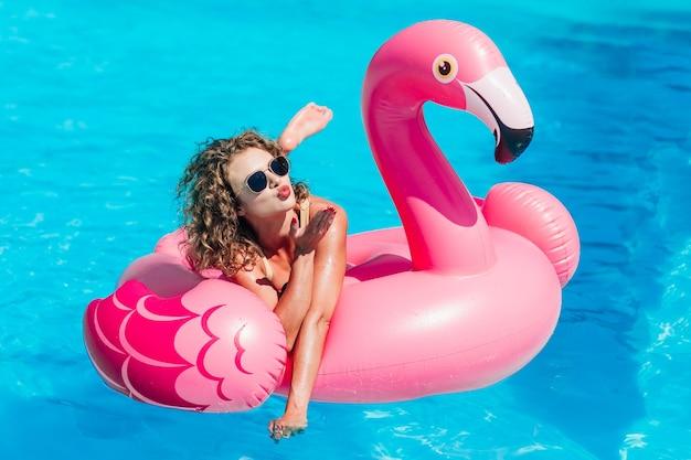 Ragazza bionda in posa per storie di instagram, che riposa nella piscina estiva su un fenicottero rosa gonfiabile in costume da bagno. dai un bacio.