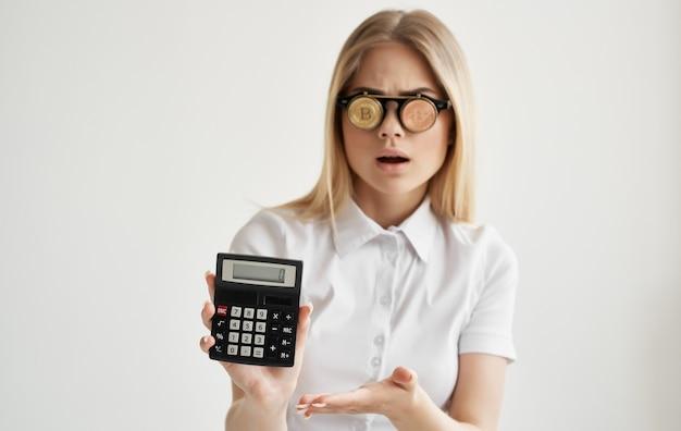 Bionda in bicchieri con una calcolatrice nelle mani della finanza bitcoin di criptovaluta.