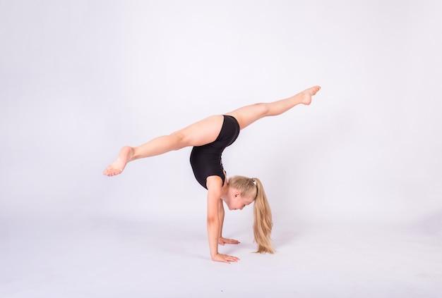 Una ginnasta bionda in costume da bagno nero esegue spaccate sulle mani su un muro bianco isolato
