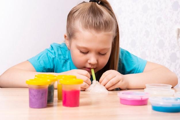 Un bambino dai capelli biondi gonfia una bolla di muco bianco