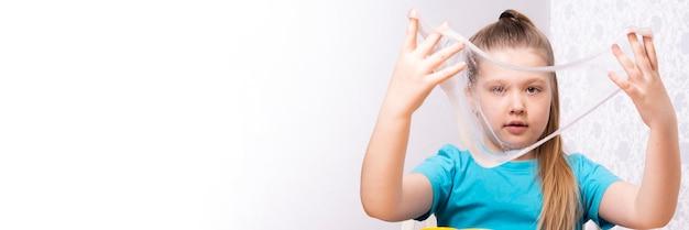 Il bambino biondo sta giocando con il muco