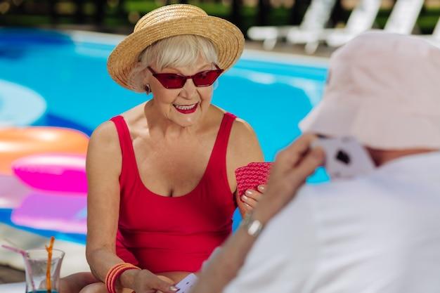 Donna alla moda bionda che indossa occhiali da sole rossi luminosi che giocano a carte con il marito