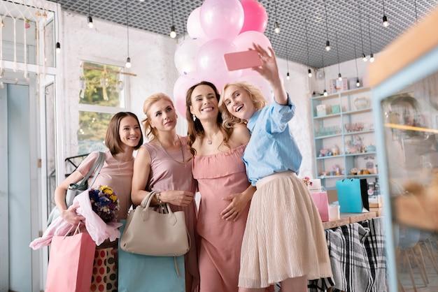Donna dai capelli biondi. donna dai capelli biondi che indossa camicia blu e gonna rosa facendo selfie con un amico in stato di gravidanza