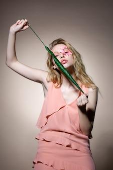 Giovane modella dai capelli biondi con fiori vicino all'occhio che tiene la foglia in posa vicino al muro