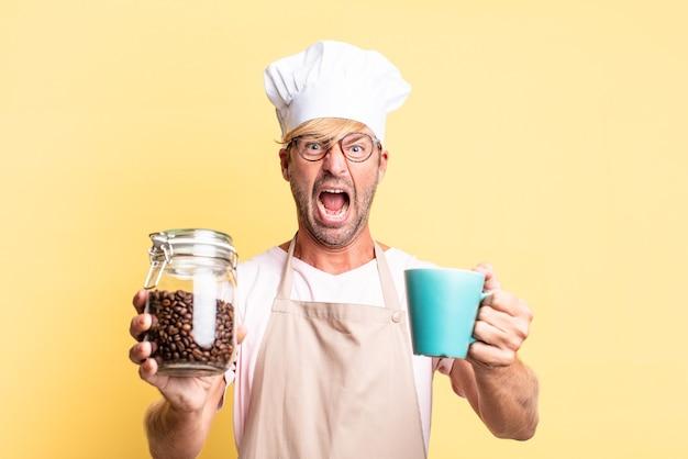 Uomo adulto biondo bello chef che tiene una bottiglia di chicchi di caffè