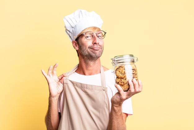 Uomo adulto biondo bello chef che tiene una bottiglia di biscotti fatti in casa