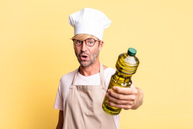 Uomo adulto biondo bello chef che tiene una bottiglia di olio d'oliva
