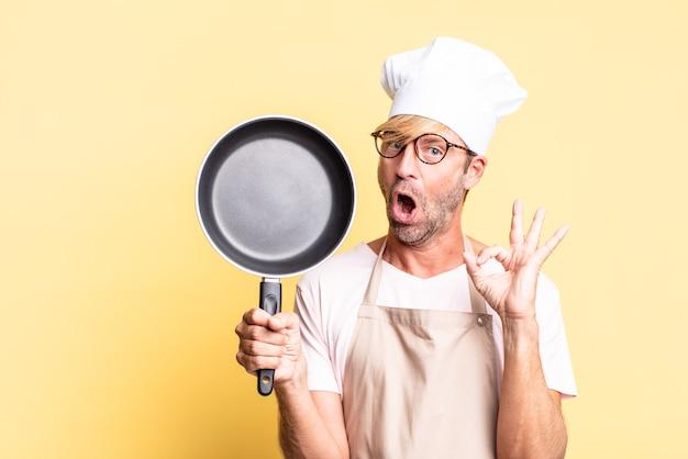 Uomo adulto biondo bello chef che tiene una padella