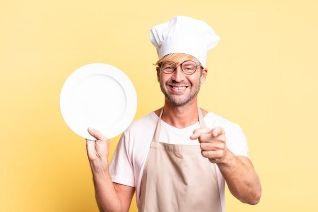Uomo adulto biondo bello chef con un piatto vuoto