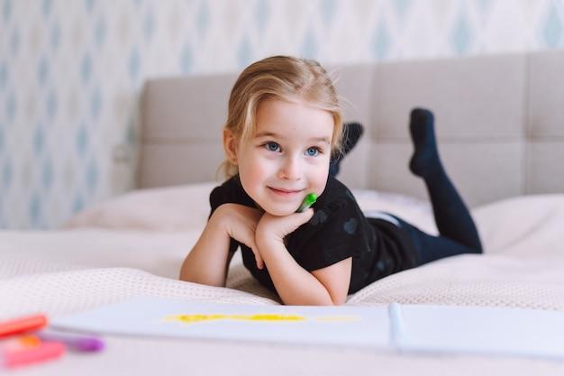 Bambina felice bionda che disegna e scrive con matite colorate sdraiate sul letto a casa e educazione prescolare, apprendimento precoce