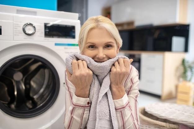 Casalinga bionda in camicia a righe che si siede vicino alla lavatrice e che sente l'odore dei vestiti puliti