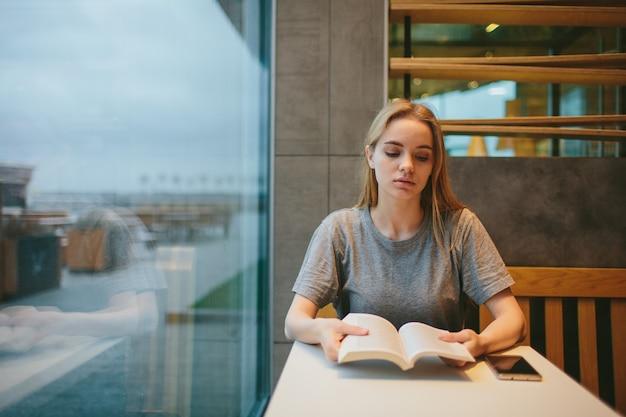 La bionda sta leggendo un libro e sta parlando al telefono in una tavola calda o in un ristorante.