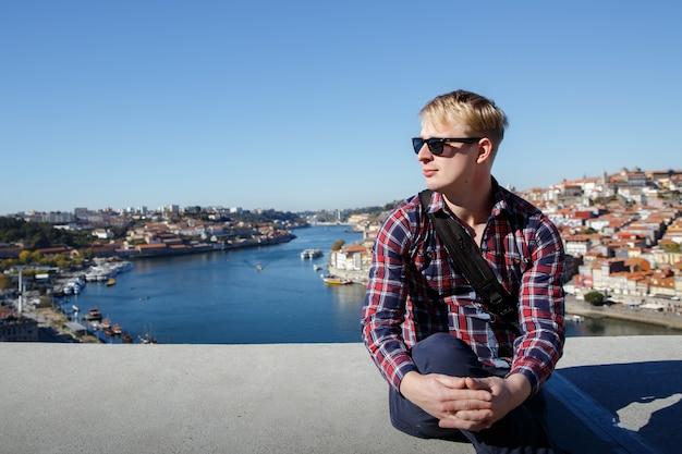 Una bionda è seduta su una città europea. occhiali da sole, camicia a quadri