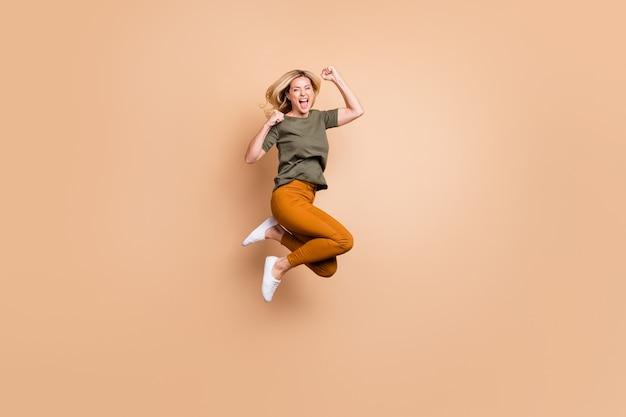 Signora bionda in posa contro il muro beige