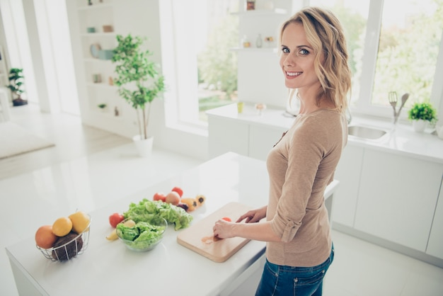 Signora bionda in posa in cucina