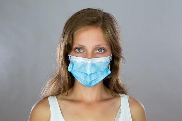 Signora bionda in mascherina chirurgica che guarda alla telecamera in studio